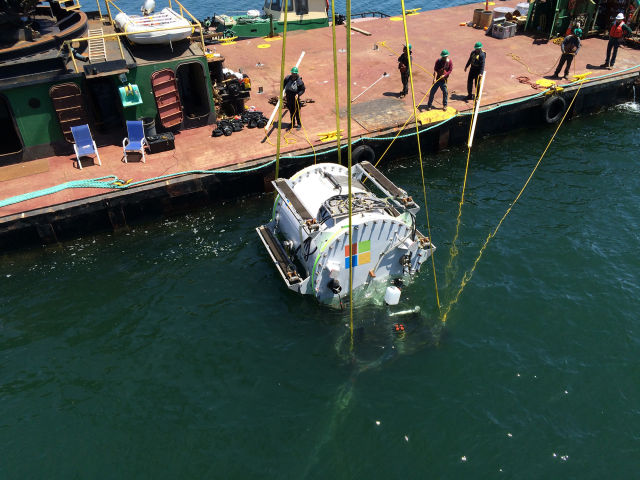 "Lowering <em>Leona Philpot</em>, Microsoft's first underwater serverpod, into the water.""><figcaption class="