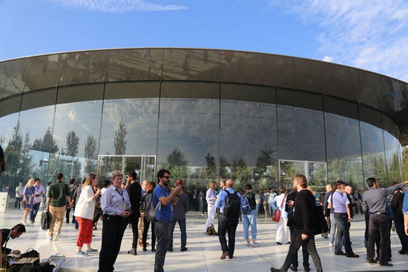 People cluster outside a futuristic glass-and-steel building.