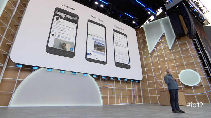 A man gives a speech on a stage in front of the image of three smartphones.