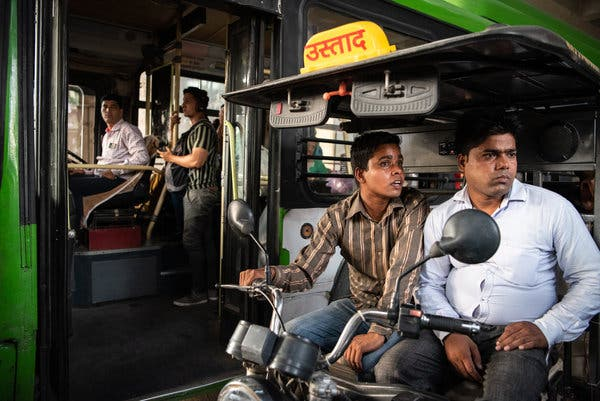 Electric rickshaw drivers must fight for space with buses and other vehicles outside Delhi metro stations.