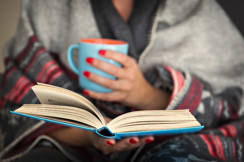Stock photo of a blanket-wrapped woman reading a book.