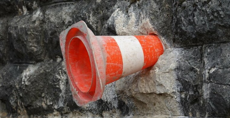 An orange traffic cone has been lodged in wall made of stone.