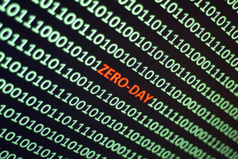 The word ZERO-DAY is hidden amidst a screen filled with ones and zeroes.